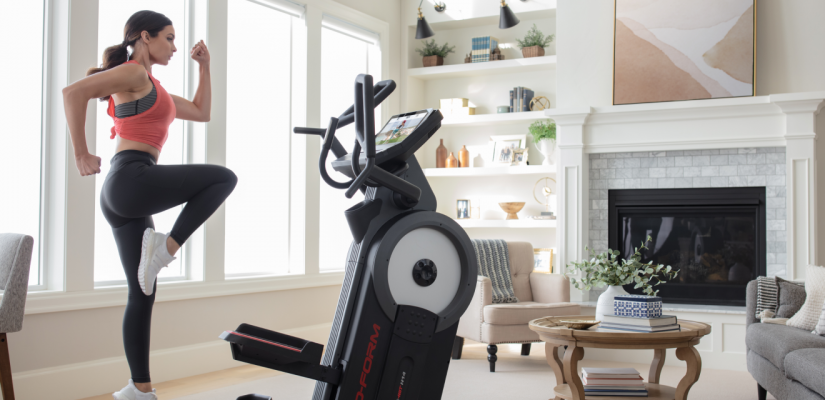 Woman using an iFit-connected elliptical during a HIIT workout