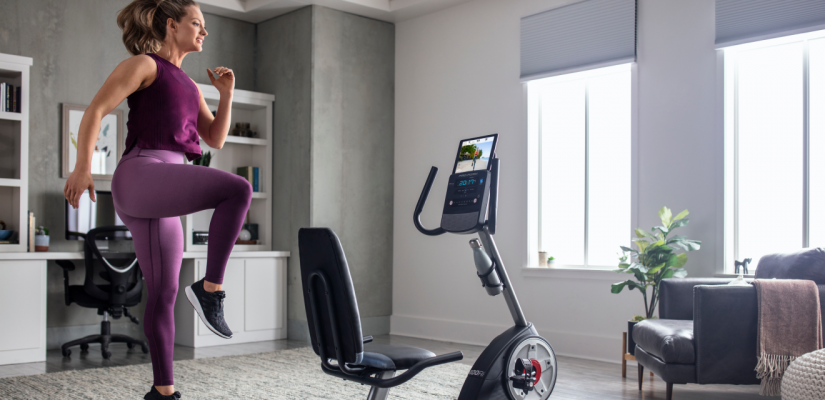 Woman does a HIIT workout using a iFit-connected bike