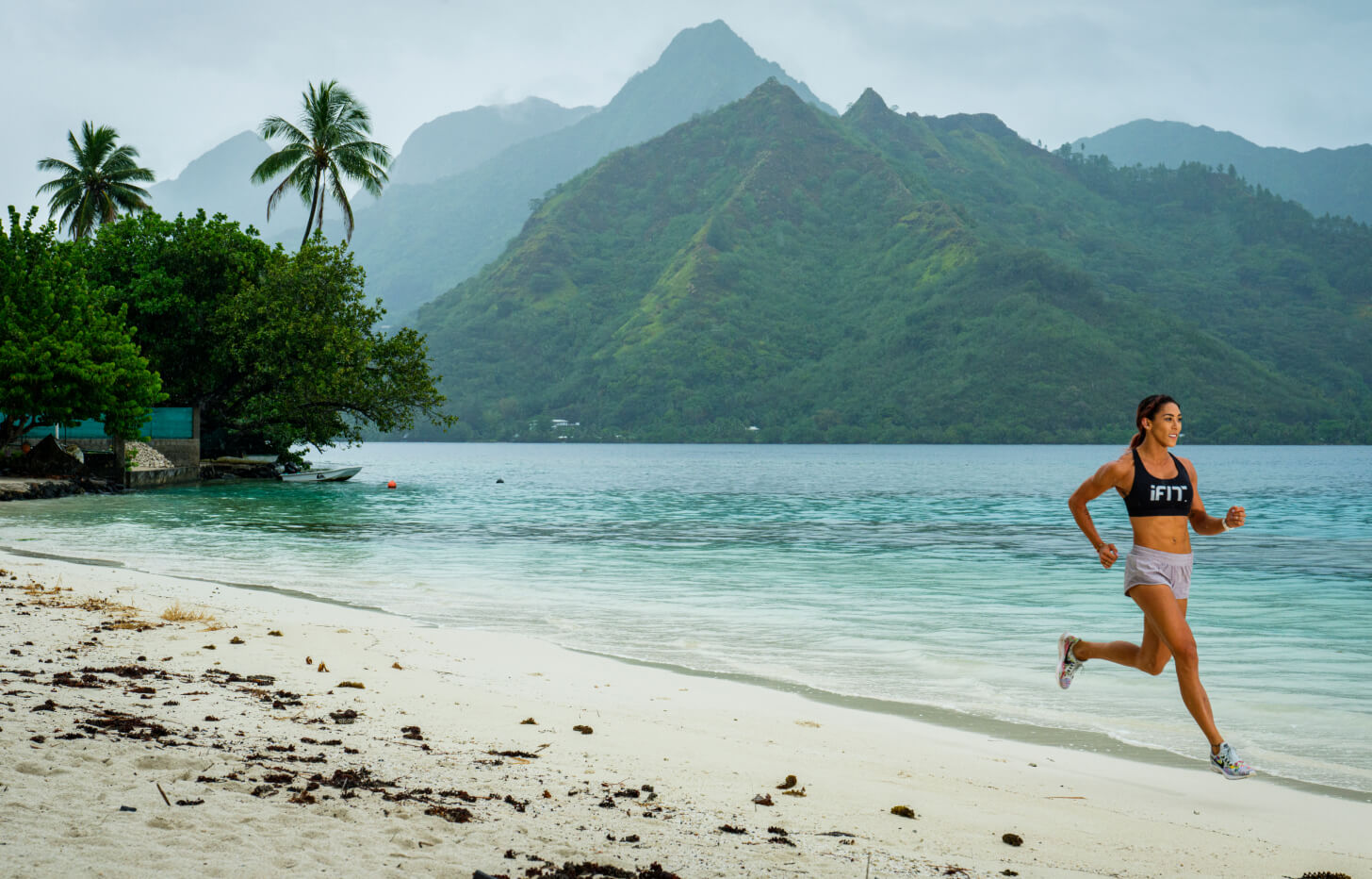 iFit trainer coaches a beach running workout