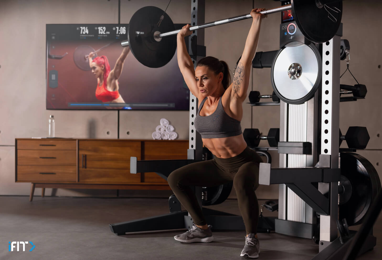 Woman completes an iFIT weight lifting workout