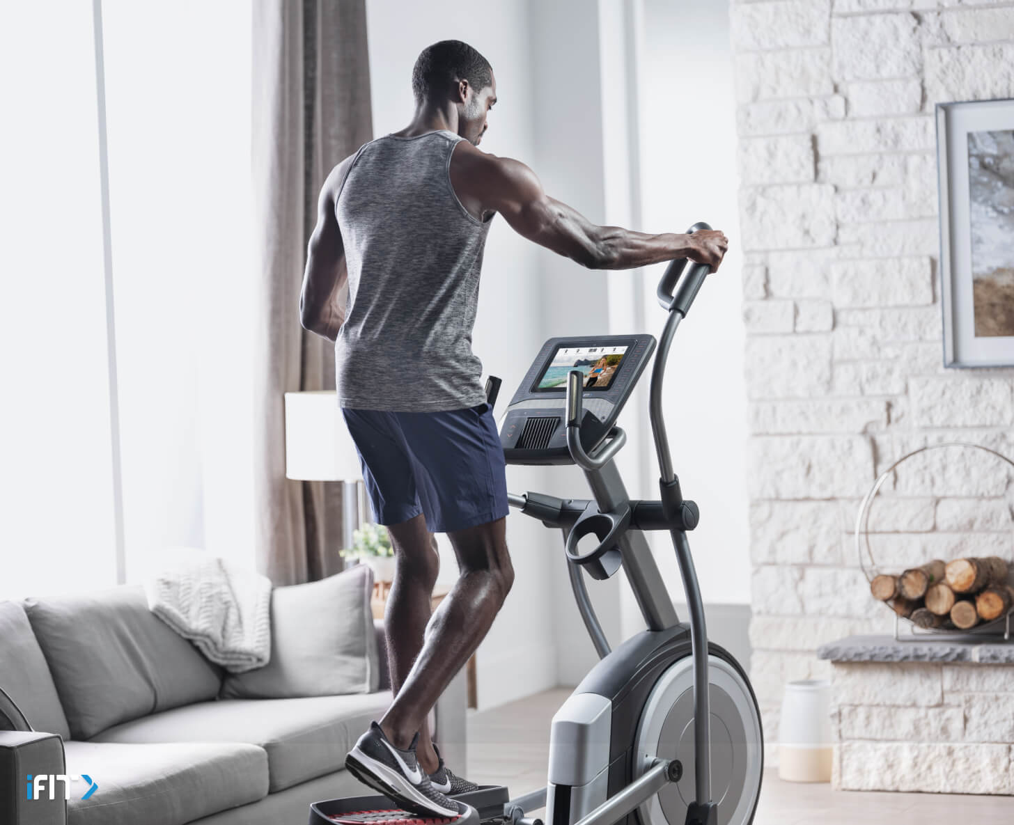 Man works out with iFIT elliptical exercises