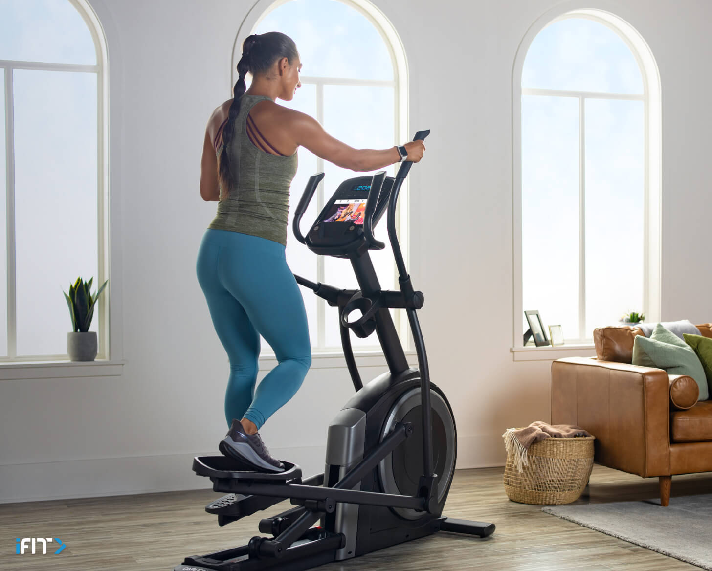 Woman does iFIT elliptical workouts